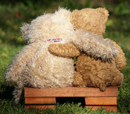 Photo for two teddy bears on a bench with arms around each other - Royalty Free Image