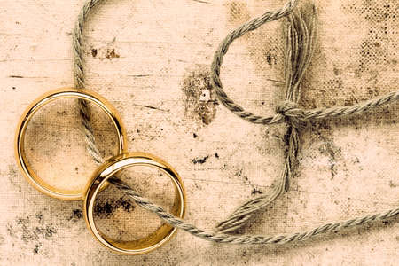 Photo for Two gold wedding rings tied with string - Royalty Free Image