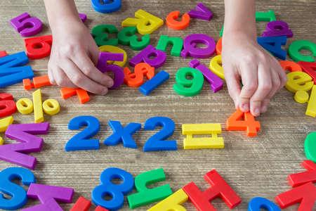 Foto de Child's hands playing with numbers, learning simple multiplication - Imagen libre de derechos