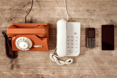 Photo pour Old telephones and modern mobile phone show evolution in telecommunications - image libre de droit