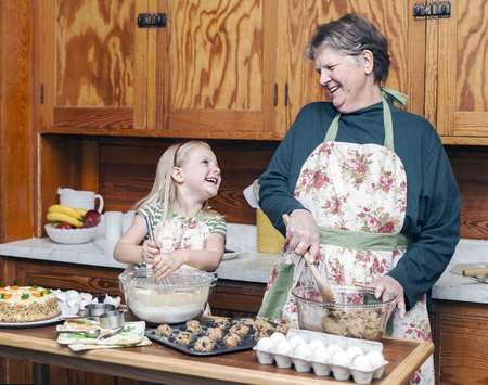Photo pour Happy grandmother and granddaughter cooking together and having fun in the kitchen - image libre de droit