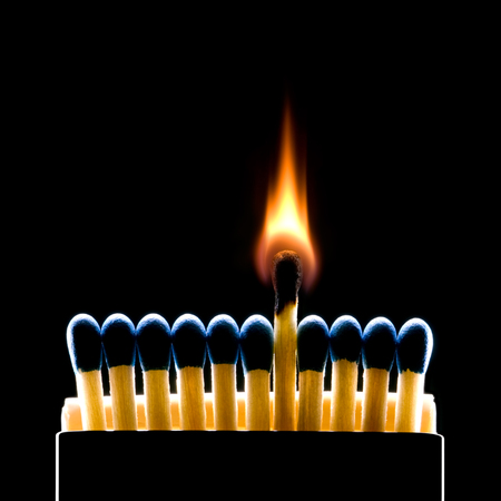 Foto de Many dark blue matches on a black background  one match burns   - Imagen libre de derechos
