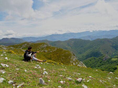 Foto de Man with a beard contemplating the mountains while resting sitting with his dog - Imagen libre de derechos