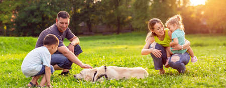 Foto per happy family is having fun with golden retriever - Happy family playing with dog in park - Immagine Royalty Free