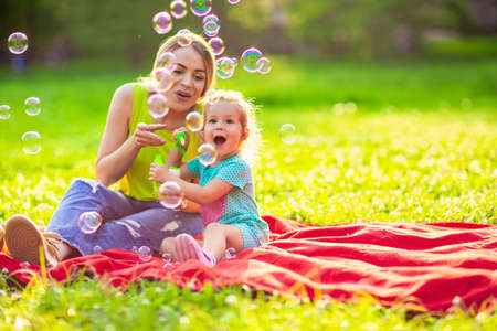 Photo pour Happy family in park -Cute female child blows soup foam and make bubbles with her mother in nature - image libre de droit