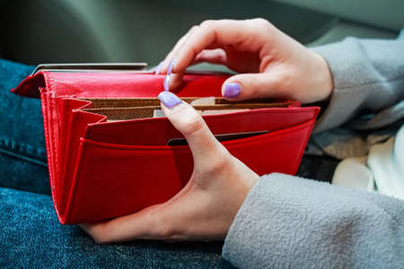 Photo for Female hands hold modern red money purse for women - Royalty Free Image