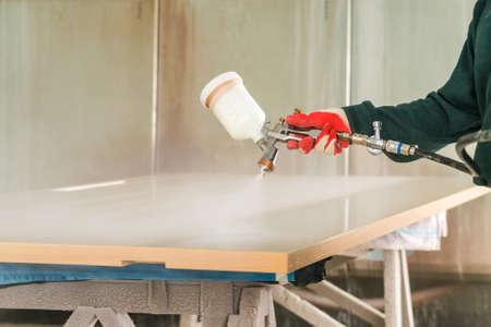 Photo pour Staining wood with spray gun - image libre de droit