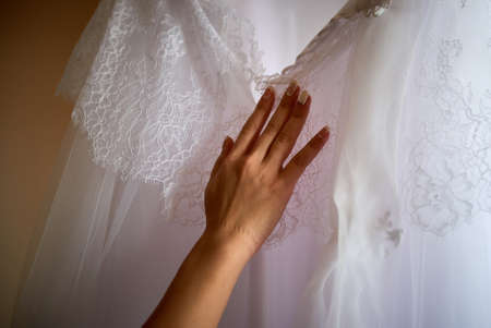 Photo for Female hand touches wedding dress close up - Royalty Free Image