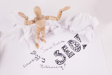Photo for SEO search engine Optimization help wooden jointed doll hands up crumbled paper - Royalty Free Image