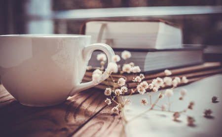 Foto de Books, flowers and white cup on wooden table - Imagen libre de derechos