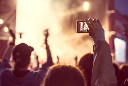 Photo pour Close up of recording video with smartphone during a concert. Toned picture - image libre de droit