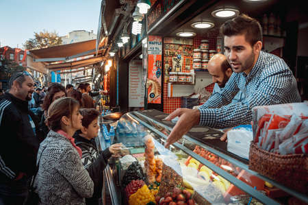 Photo pour ISTANBUL, TURKEY -  october 23, 2014: Vendor sales ice-cream at street market in Ortakoy aquare in Istanbul, Turkey. - image libre de droit