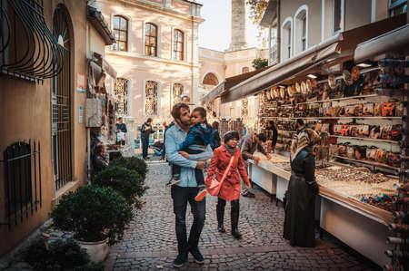 Foto de ISTANBUL, TURKEY -  october 23, 2014: Father walks with his children along the street market in Ortakoy aquare in Istanbul, Turkey. Toned image. - Imagen libre de derechos