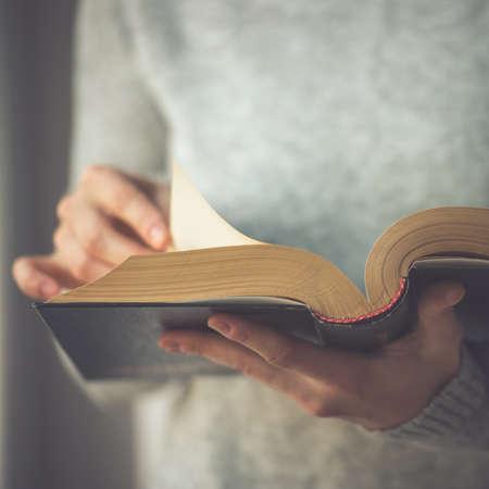 Foto de Young woman reading a book. Toned image - Imagen libre de derechos