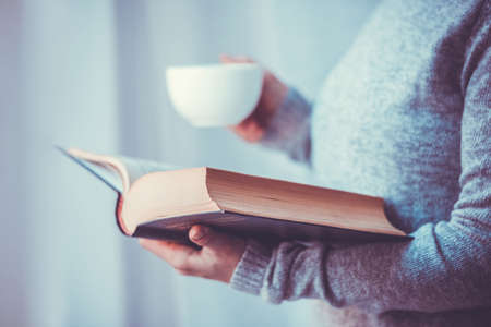 Photo for Young woman reading a book and holding cup of tea or coffee. Toned image - Royalty Free Image