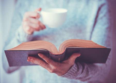 Foto de Young woman reading a book and holding cup of tea or coffee. Toned image - Imagen libre de derechos