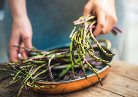 Photo pour Hands holding a bunch of fresh asparagus. Selected focus - image libre de droit