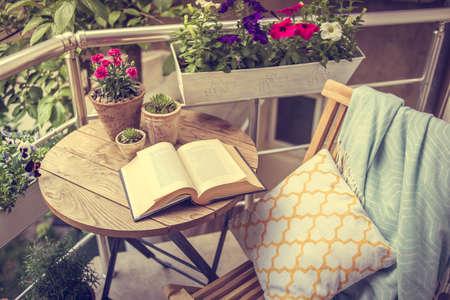 Foto de Beautiful terrace or balcony with small table, chair and flowers. Toned image - Imagen libre de derechos
