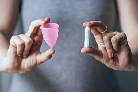 Foto für Young woman hands holding different types of feminine hygiene products - menstrual cup and tampons - Lizenzfreies Bild