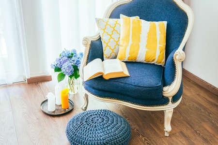 Foto de Cozy armchair with open book and decorative pillows. Interior and home decor concept - Imagen libre de derechos