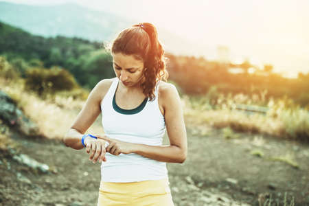 Foto de Woman using activity tracker. Outdoor fitness concept. Toned image - Imagen libre de derechos