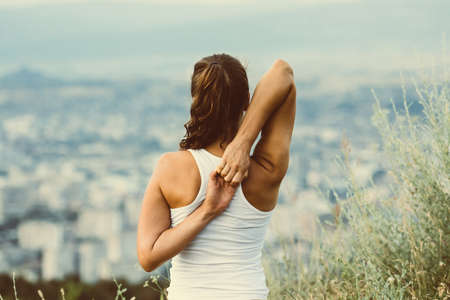 Photo for Young woman sits in yoga pose with city on background. Freedom concept. Calmness and relax, woman happiness. Toned image - Royalty Free Image