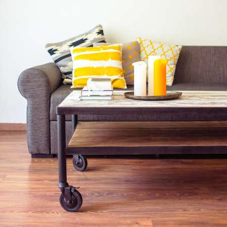 Foto de Modern wooden coffee table and cozy sofa with pillows. Living room interior and home decor concept - Imagen libre de derechos
