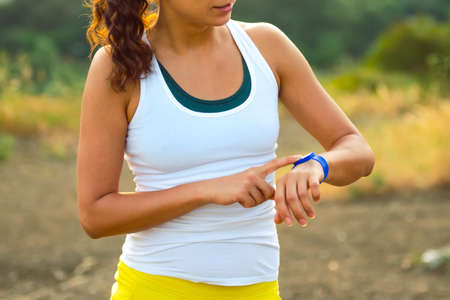 Foto de Woman using activity tracker. Outdoor fitness concept - Imagen libre de derechos