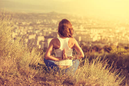 Foto de Young woman sits in namaste yoga pose with city on background. Freedom concept. Calmness and relax, woman happiness. Toned image - Imagen libre de derechos