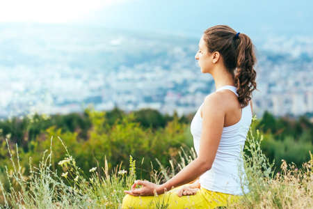 Photo pour Young woman sits in yoga pose with city on background. Freedom concept. Calmness and relax, woman happiness. - image libre de droit