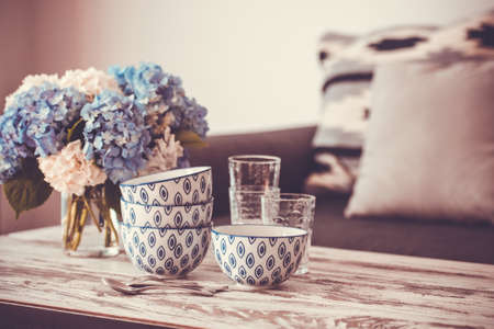Photo for Bouquet of hortensia flowers and glass bowls on modern wooden coffee table and cozy sofa with pillows. Living room interior and home decor concept. Toned image - Royalty Free Image