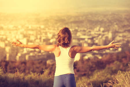 Foto de Young woman spreading hands wide open with city on background. Freedom concept. Love and emotions, woman happiness. Toned image - Imagen libre de derechos