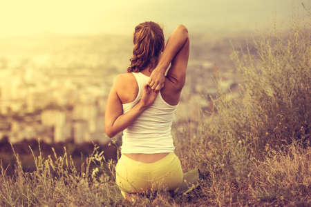 Foto de Young woman sits in yoga pose with city on background. Freedom concept. Calmness and relax, woman happiness. Toned image - Imagen libre de derechos