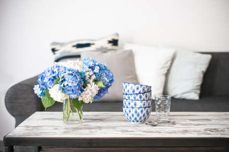 Foto de Bouquet of hortensia flowers and glass bowls on modern wooden coffee table and cozy sofa with pillows. Living room interior and home decor concept - Imagen libre de derechos