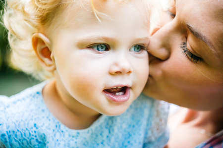 Photo for Young beautiful mother kisses her toddler blonde daughter during a walk outdoors - Royalty Free Image