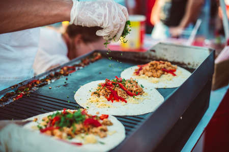 Foto de Preparation of fajitas, mexican beef with grilled vegetable in tortilla wraps. Street food and outdoor cooking concept - Imagen libre de derechos