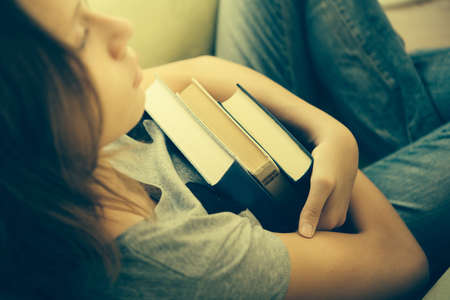 Foto de A sad teenage girl sits in armchair holding books. Toned image - Imagen libre de derechos