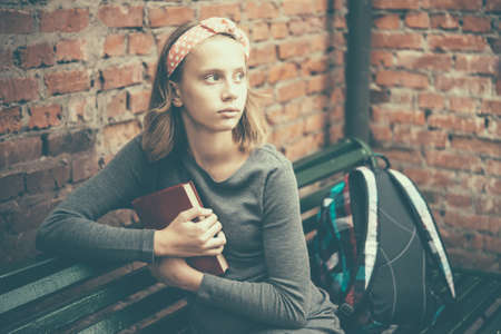 Foto de A portrait of a teenage girl sitting on a bench holding a book with brick wall in the background. Toned image - Imagen libre de derechos
