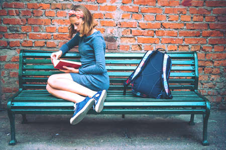 Photo pour A teenage girl is reading on a bench with brick wall in the background. Toned image - image libre de droit