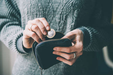 Photo for Hands holding british pound coin and small money pouch. Toned picture - Royalty Free Image