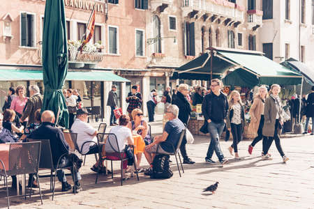 Foto de VENICE, ITALY - OCTOBER 11: People are sitting at the outside terrace of a small cafe in Venice, Italy. Toned picture - Imagen libre de derechos