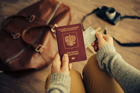 Foto de Person holds Russian travel passport and plastic credit card in hands with leather bag and photo camera in the background. Travel and tourism concept. Toned picture - Imagen libre de derechos