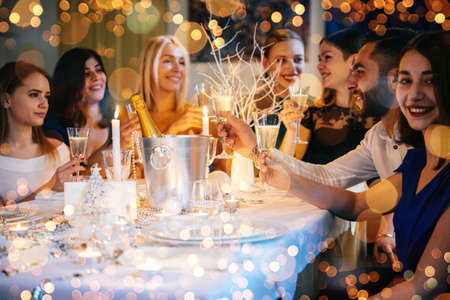 Photo pour Friends celebrating Christmas or New Year eve. Party table with champagne. - image libre de droit