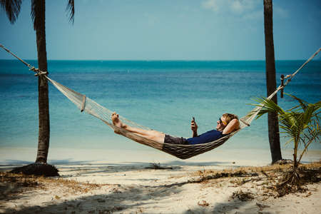 Photo pour A young man relaxes in a hammock at the beach while checking messages on his smartphone. Toned image - image libre de droit