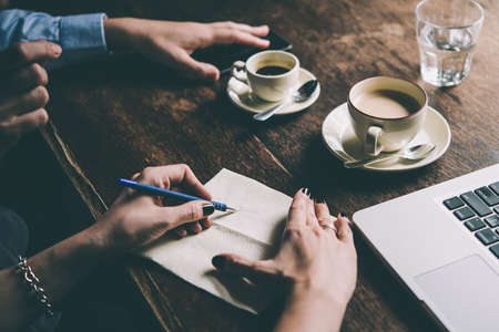 Foto de Two women discussing business projects in a cafe while having coffee. Startup, ideas and brain storm concept. Toned picture - Imagen libre de derechos