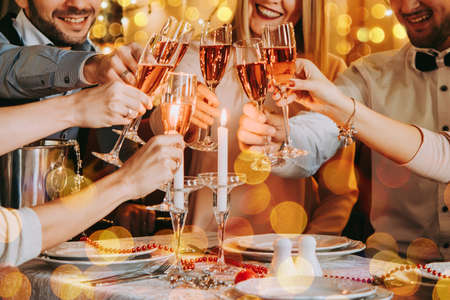 Photo pour Friends celebrating Christmas or New Year eve. Party table with rose champagne. - image libre de droit