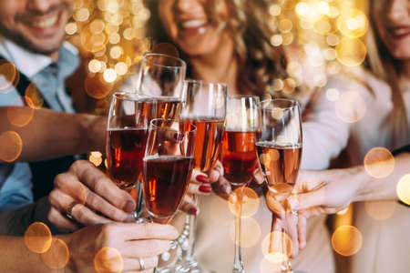 Photo pour Friends celebrating Christmas or New Year eve with glasses of rose champagne - image libre de droit