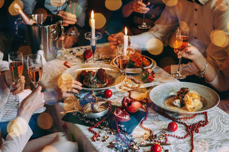 Photo for Friends celebrating Christmas or New Year eve. Party table with rose champagne. - Royalty Free Image