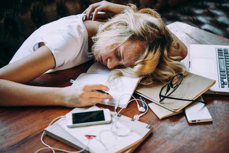 Foto de A tired teenage girl sleeping on her table while doing her school homework. Laziness and procrastination concept - Imagen libre de derechos