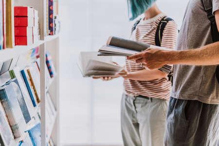 Foto de People looking through books at a library or a book store. - Imagen libre de derechos